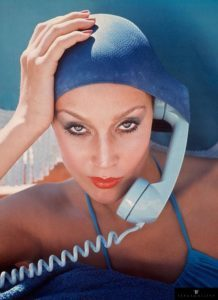 American model Jerry Hall poses with a telephone in Jamaica for British Vogue, 1975.