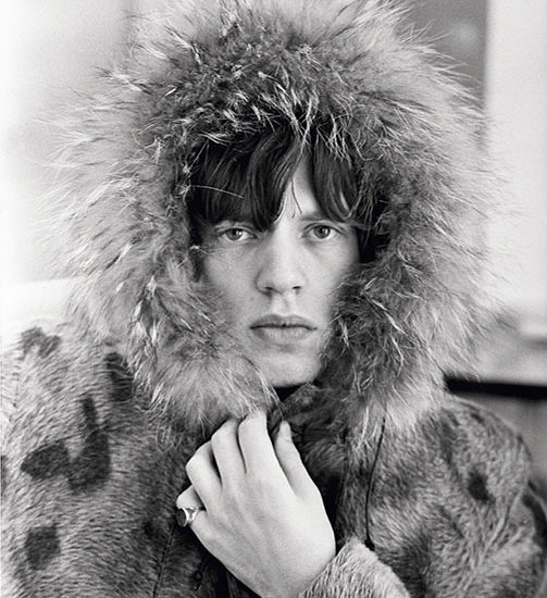 Rolling Stones singer Mick Jagger posing in a fur parka